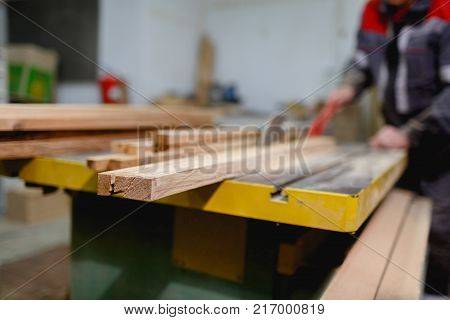 Part of a sawn-off board close-up that saws the worker on a blurred background on the machine