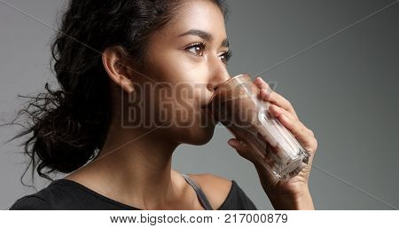 Laughing attractive Middle Eastern girl in relaxed black top drinking mocca, hot chocolate, caffee from a tall glass isolated on gray