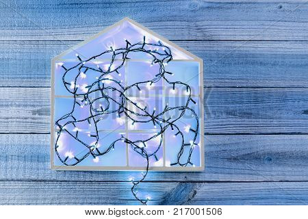 Fairy Lights and House Symbol on Wooden Background