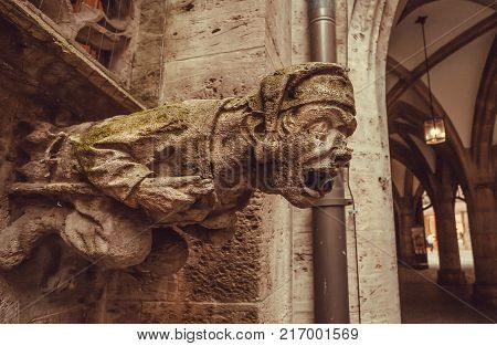 Grotesque carved waking-up human figure projecting from the gutter of a building. Stone gargoyle on building in Bavaria, Germany.