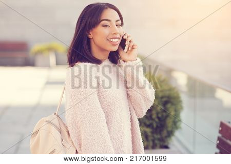Phone call. Positive nice cheerful woman putting a cell phone to her ear and listening to her interlocutor while being outside