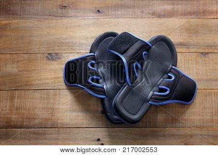 Pair of Black Slippers on Wooden Background