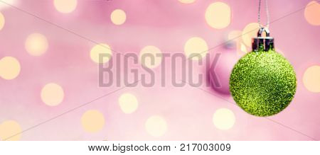 Picture of New Year's pink and green balls on pink background with spots.