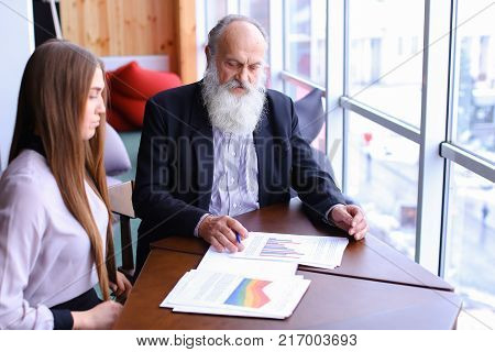 Man signs document to lay his age with young assistant with papers in office in winter.Beautiful stately grey head man with long beard and young attractive blond girl with longhair in business suit sitting at table in studio in modern workspace. Concept o