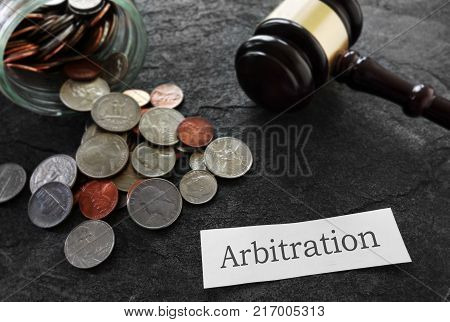 Coins and legal gavel with Arbitration news headline