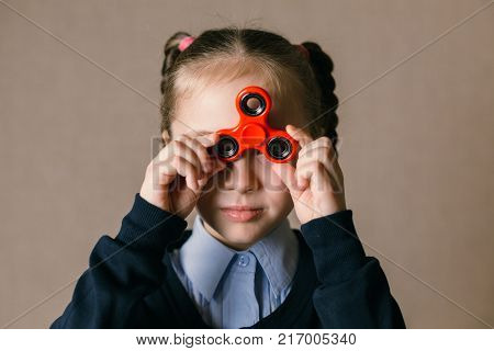 Little caucasian school girl with Fidget Spinner held up to his eyes