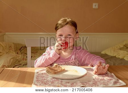 Kid girll eats chocolate cream spread on bread. Chocolate sweet food snack. Happy girl has a snack in the kitchen. A cute small girl smiles. A small girl with chocolate cream stains on face. Playful little girl wears clown nose. Childhood and fun concept
