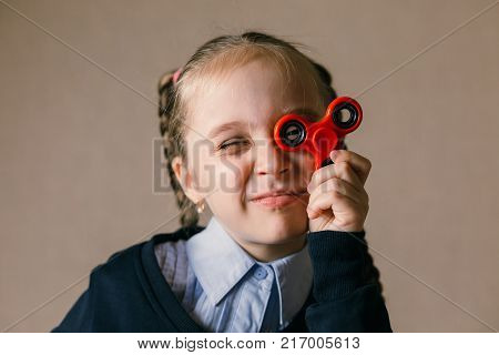 Little caucasian girl with Fidget Spinner held up to his eyes