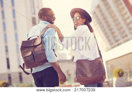 Pleasant date. Cheerful nice positive couple smiling and having a walk while being on a date