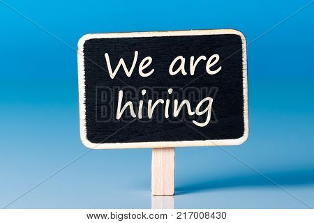 Job recruiting advertisement represented by WE ARE HIRING texts on wooden plaque. Announcement of hiring position to be recruited and filled.