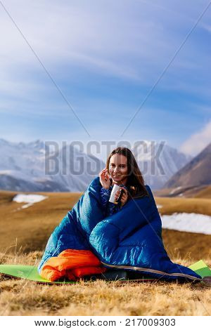 happy young girl traveler sits in a sleeping bag drinking tea from a thermo mug on a background of the Caucasian mountains