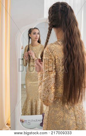 A beautiful girl looks in the mirror, unravels her hair. Preparation for the holiday