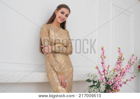 Fashionable young beautiful girl is smacked on a white background in a chic evening dress