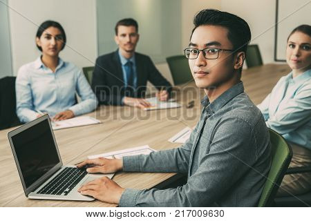 Portrait of serious young Asian businessman sitting at table in boardroom with his multiethnic team, working on laptop and looking at camera