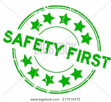 Grunge green safety first wording with star icon round rubber seal stamp on white background