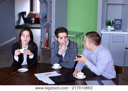Two guys and beautiful girl, students or classmates communicate and laugh, sitting at table and drinking tea or fragrant coffee with course projects and graphics in library during change. Two men joke and show their hands to distance, they look to side. E