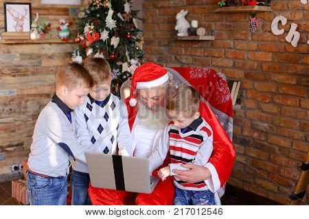 Brothers boys and sister girl help old Christmas grandfather to choose interesting gifts for holidays in decorated room with high floor lamp, walls on which posters hang, dressed up tree, under New Year surprises lie boxes tied ribbons. Father gray long b