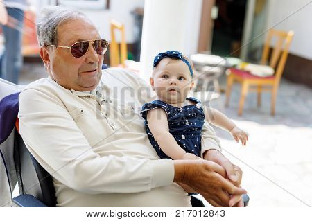 Cute little baby girl with grandfather on wheelchair on summer day in garden. Happy senior man holding smiling child on arm.