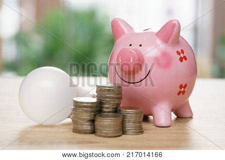 Piggy bank with light bulb and stack coins on wooden desk - save energy concept