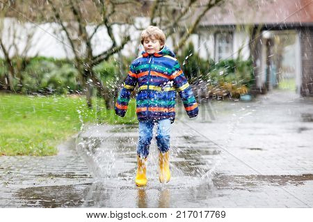 Little kid boy wearing yellow rain boots and walking during sleet, rain and snow on cold day. Child in colorful fashion casual clothes jumping in a puddle. Having fun outdoors.