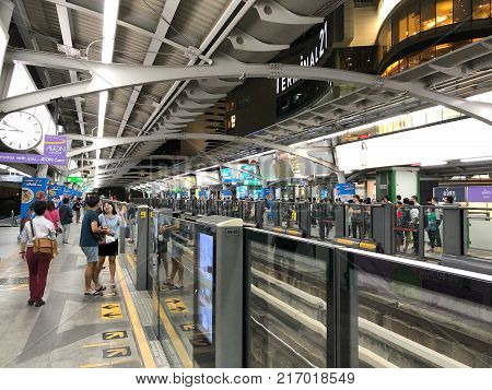 BANGKOK, THAILAND - DEC 06, 2017: Rail travellers wait for an approaching BTS Skytrain at a city centre station. The Thai capital's BTS rail public transport system serves 600,000 passengers daily