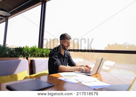 Prosperous financial manager enjoying new project idea and working with laptop and documents. Attractive successful man wears black shirt and watch, sitting at cafe table. Concept of clear budgetary planning, providing financial guidance and support to cl
