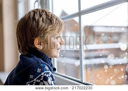 Happy adorable kid boy sitting near window and looking outside on snow on Christmas day or morning. Smiling child fascinated with snowfall and big snowflakes.