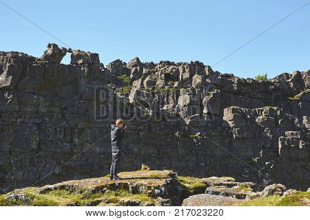 tourist walking and photographing in fracture of tectonic plates in national park Thingvellir in Iceland. excursion to the national park Thingvellir in Iceland