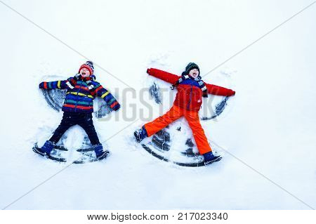 Two little siblings kid boys in colorful winter clothes making snow angel, laying down on snow. Active outdoors leisure with children in winter. Happy brothers with warm hat, gloves, winter fashion