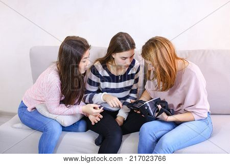 Attractive girls hold modern devices, VR glasses and inspect, study possibilities of gadget and communicate with each other, sitting on gray sofa in room during day. European-looking girl with medium-length blond hair dressed in pink blouse and jeans, sec