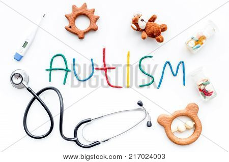 Childhood diseases. Word autism near stetoscope, pills, toys on white background top view.