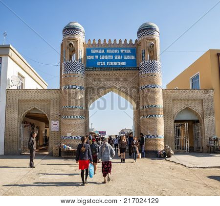 KHIVA UZBEKISTAN - OCTOBER 22 2016: East gate of the fortress Dishan-Kala the outer town of Khiva now the entrance to the city bazaar. Many unidentified people come in and out through the gate