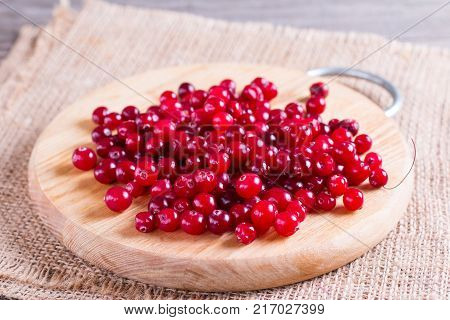 Fresh cranberry (cowberry) on wooden background selective focus