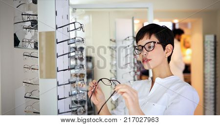health care, eyesight and vision concept - happy beautiful woman choosing glasses at optics store