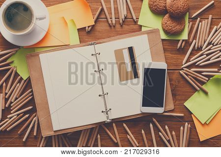 Buying stationery online. Top view on designer workplace with credit card, lots of pencils, mobile, open sketchbook, sticky memo notes and cup of morning coffee with cookies on wooden desk background