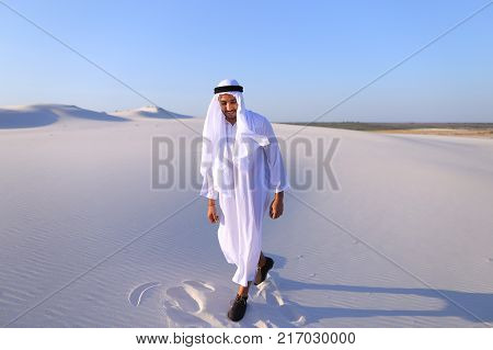 Handsome Arab man dances on spot and drives feet along soft white sand in middle of bottomless desert. Guy sheikh smiles and laughs, rejoices and jumps in national costume, which develops in wind. Swarthy Muslim with short dark hair dressed in kandura, lo