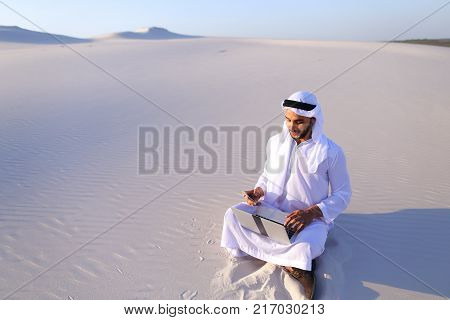 Successful young businessman male Muslim uses laptop to build drawing and prints fingers on laptop sitting on white sand in bottomless wide desert in afternoon against blue sky. Swarthy Muslim with short dark hair dressed in kandura, long, sp