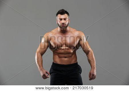 Portrait of a confident strong shirtless male bodybuilder standing and looking at camera isolated over gray background