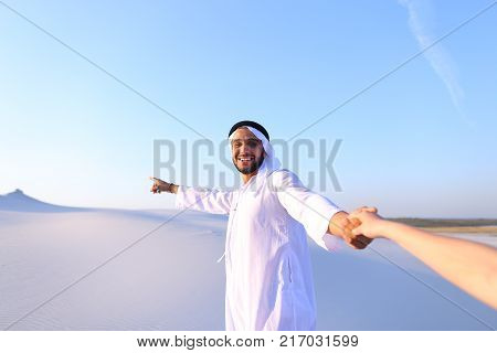 Cheerful Arab male with kindly smile on face leads woman's arm from camera and shows desert landscapes, conducts outing in middle of bottomless sandy desert with white clean sand against blue sky in open air.