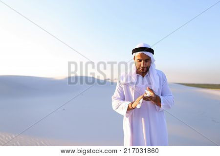Sad handsome young man, sheikh ill with cold and feels unwell, eases breathing with handkerchief and looks to side, standing in middle of bottomless desert with snow-white sand on sunny summer day. Swarthy