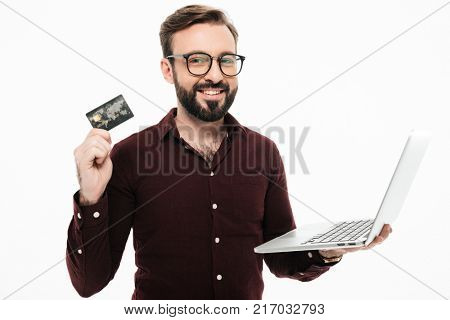 Photo of smiling young man standing isolated over white background. Looking camera holding debit card and laptop computer.