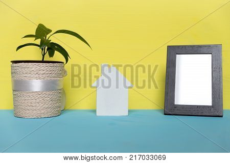 Dream of own house concept. Small wooden house photo frame and house plant on colorful background