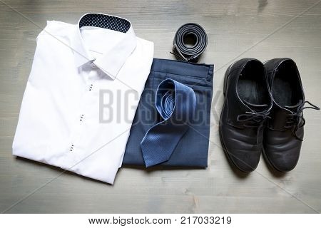 Folded businessman's clothes and shoes. White shirt blue pants leather belt and blue tie