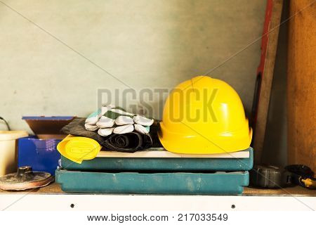 Attic construction and renovation tools yellow safety helmet gloves tool box measuring tape and other tools.