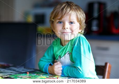 Little blond kid boy playing together board game at home. Funny child having fun. beautiful toddler learning interact, win and lose.