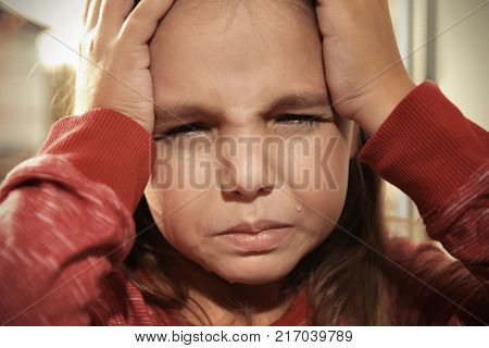 Little sad girl crying. Abuse of children concept