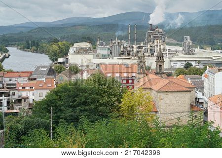 PONTECESURES, SPAIN -SEPTEMBER 10, 2017: Cityscape of Pontecesures with old church and large factory on the Camino de Santiago trail on September 10, 2017 in Galicia, Spain