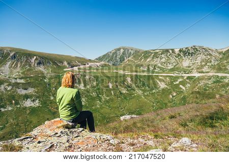 Woman sits on the top and admires the beautiful view of Parang mountains Romania