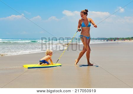 Happy family having fun - mother run and pull baby son on surfing board by water pool along sea surf of beach. Active parents and kids lifestyle people activity on summer beach holiday with children