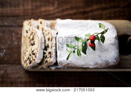 high-angle shot of a stollen cake for christmas time sprinkled with icing sugar, placed on a wooden rustic table